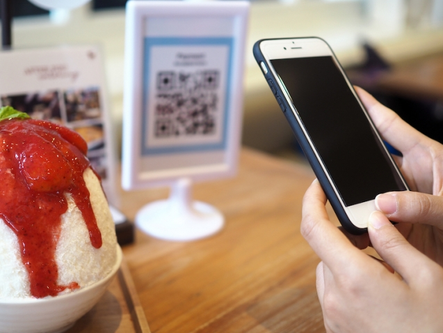 Hands use the phone to scan the QR code to receive discounts from Binsu orders in the cafe.